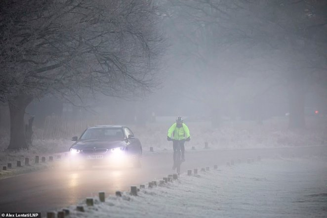 Drivers and cyclists travel through Richmond Park in South West London as it experiences a foggy start this morning
