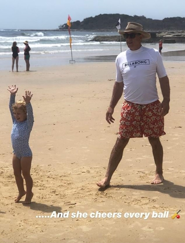 Bonding time! In another, Poppy is pictured playing cricket with Phoebe's dad Mitchell (right) on the sand