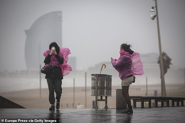 Two woman walk along the promenade of Barcelona where the 'Gloria' storm has left strong gusts of wind and rain on January 21, 2020 in Barcelona, Spain