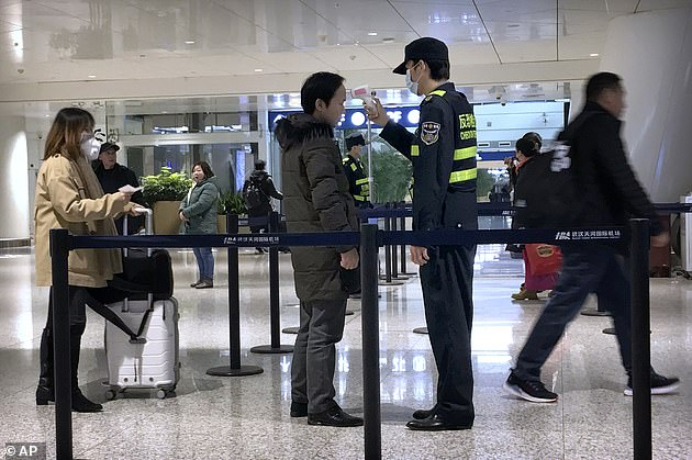 An official uses an infrared thermometer on a traveler at a health screening checkpoint at Wuhan Tianhe International Airport. Wuhan is at the centre of the outbreak