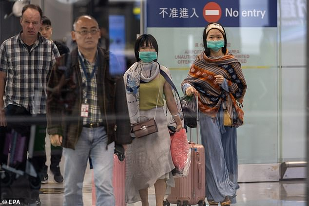 Travellers wear masks in the arrival hall of the Hong Kong International Airport today
