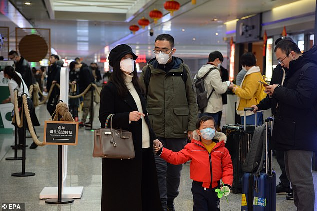 Passengers wear masks during peak spring festival travel at the Hongqiao Railway Station during peak spring festival travel in Shanghai today