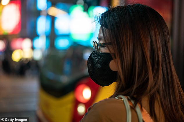 A single Chinesepatient gave the new coronavirus to 14 healthcare workers, raising concerns the person may be a 'super spreader' capable of transmitting to many people through casual contact. Pictured: a Hong Kong resident wears a protective mask after two cases were confirmed there (fi8le)