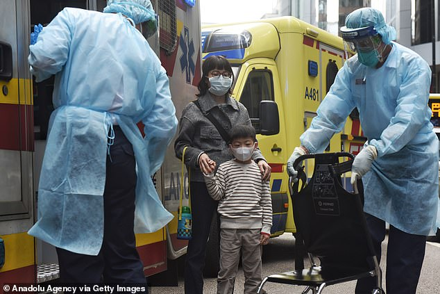 A picture captured today shows healthcare workers fitted with face masks helping a mother and child in Hong Kong
