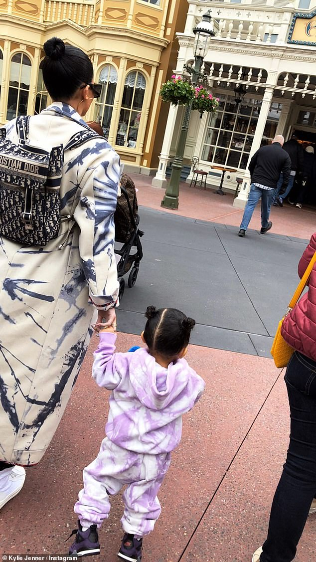 Doting mom: Kylie kept daughter Stormi close to the vest as made their way around the Happiest Place On Earth earlier this week