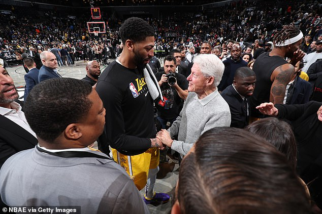 Another Lakers star Anthony Davis is seen shaking hands with the former president, Bill Clinton as other players, fans and member of the media gather around