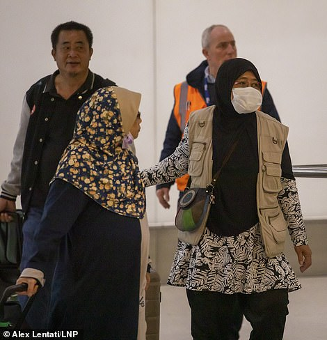 Passengers are pictured arriving at Heathrow Terminal 4 today wearing protective masks as signs have been installed around the airport warning passengers of the symptoms of the virus