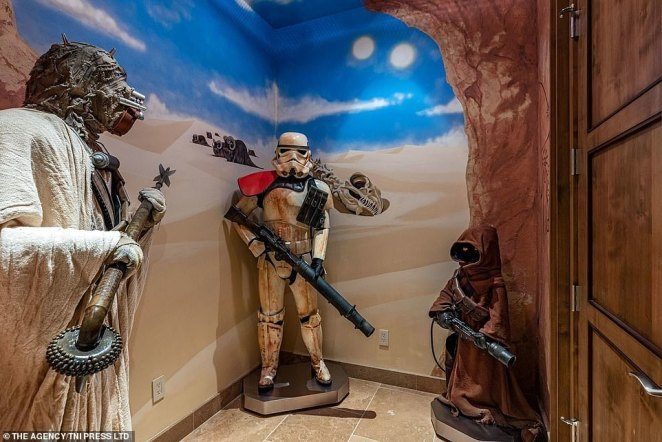 In the back of this room in the multi-million dollar mansion can be seen some key characters from the movie franchise, including a stormtrooper, a member of the Galactic Empire's armed forces, and a Jawa (right), a meter-tall humanoid that was frequently seen combing the desert for scrap materials