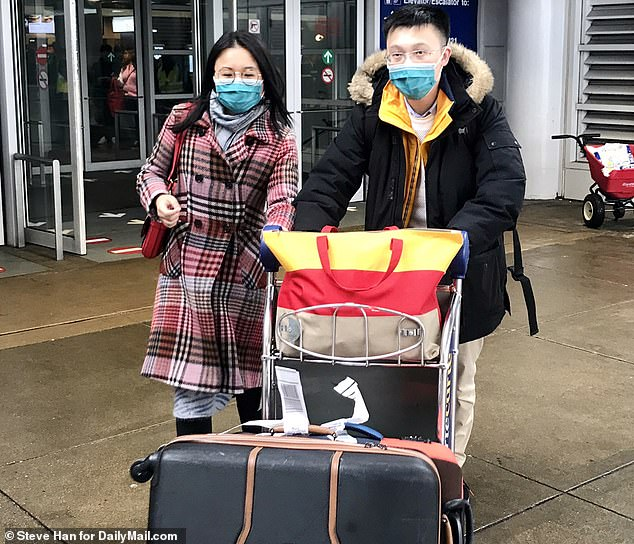 The second US case of coronavirus has been confirmed in a 60-year-old woman who traveled to Chicago, Illinois, from Wuhan, China - where the virus originated. Pictured: Passengers wearing masks arrive at O'Hare International Airport, Thursday