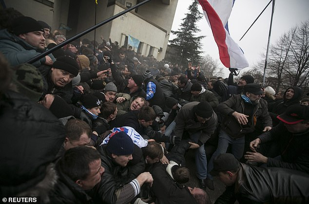 The social media-sourced data could also reveal those areas where dispatching forces would have lead to greater resistance and corresponding casualties and costs. Pictured, protesters clash outside of the Crimean parliament building inSimferopol on February 26, 2014