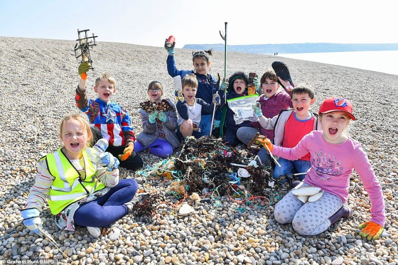 Flash mob: Youngsters on Chesil Beach, Dorset, celebrate after successfully removing plastic pollution from the coastline