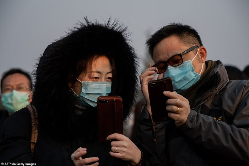 A man and a woman pictured wearing face masks as they look at their smartphones in Jingshawn park overlooking Beijing's forbidden city