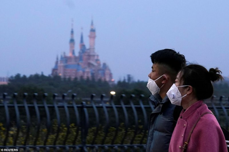Shanghai's Disneyland will close to visitors tomorrow for 'the prevention and control of the disease outbreak'.Visitors wearing masks walk past the resort today which has taken the extraordinary step of closing during the Chinese Lunar New Year holiday