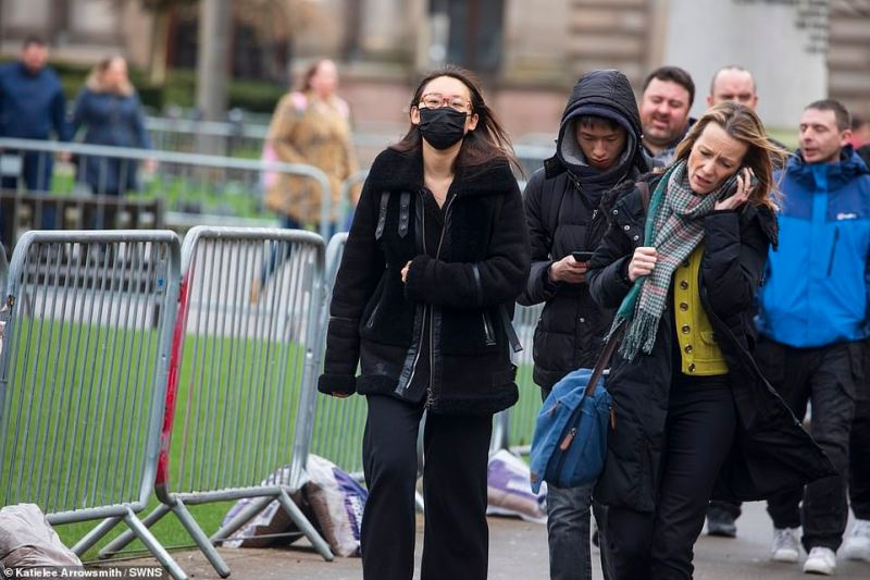 A woman in Glasgow's George Square wears a face mask today. Five patients in Scotland were tested for coronavirus after returning from China with flu-like symptoms