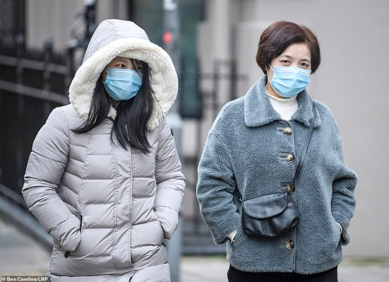 Two women are seen wearing protective face masks as they walk through the streets of central London this morning
