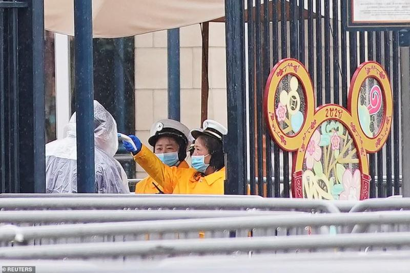 Members of staff check the temperature of a staff member at an entrance of the Shanghai Disney Resort, that is closed today during the Chinese Lunar New Year holiday following the outbreak of a new coronavirus, in Shanghai, China