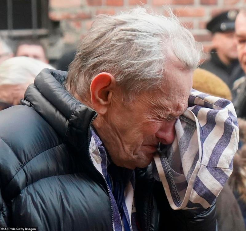 An elderly survivor cries and wipes his face with the cloth hat, which many of them were wearing to symbolise the garments they wore as prisoners during World War Two