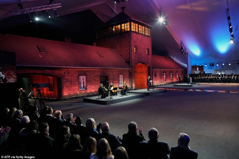 The infamous railway arch entrance to the death camp formed the backdrop of the stage this evening as a quartet played music at the memorial service