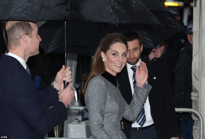 The Duke and Duchess smiled as they hid from the rain under umbrella while walking along the cobbles outside Central Hall