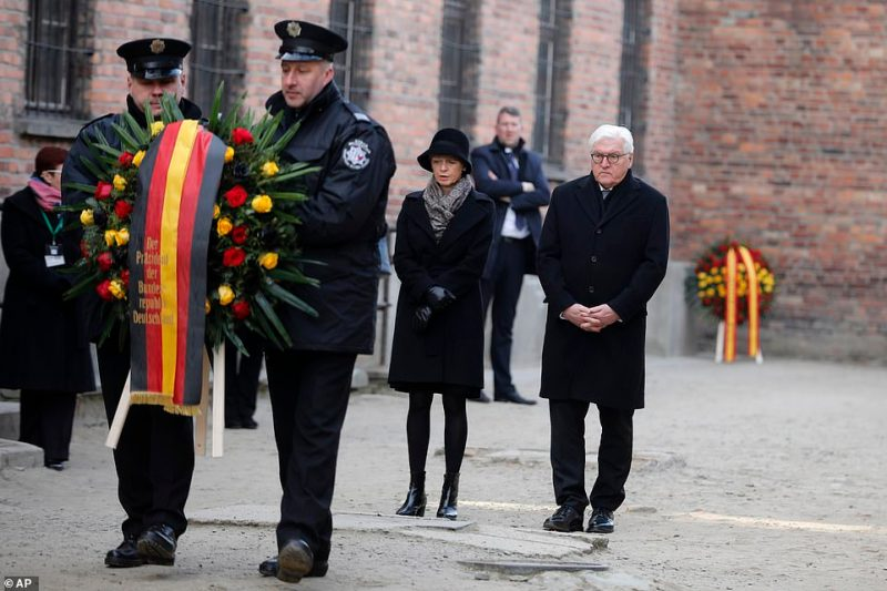 Germany's President Frank-Walter Steinmeier, with his wife Elke Buedenbender, lays a wreath at the Death Wall at the Auschwitz death camp