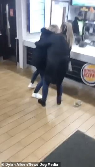 A second woman tried to restraint the woman that had climbed over the counter