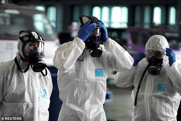 Officials at Thailand's Bangkok airport prepare to disinfect the cabin of an aircraft to prevent the spread of coronavirus on Tuesday