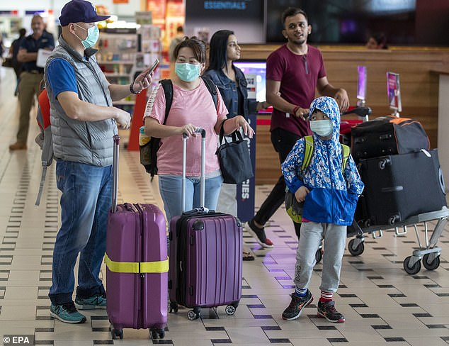Australia's gateways, major tourist destinations, universities and suburbs with large numbers of Chinese in Sydney and Melbourne have emerged as the frontline in the fight against deadly coronavirus. Passengers are pictured at Brisbane Airport on Friday