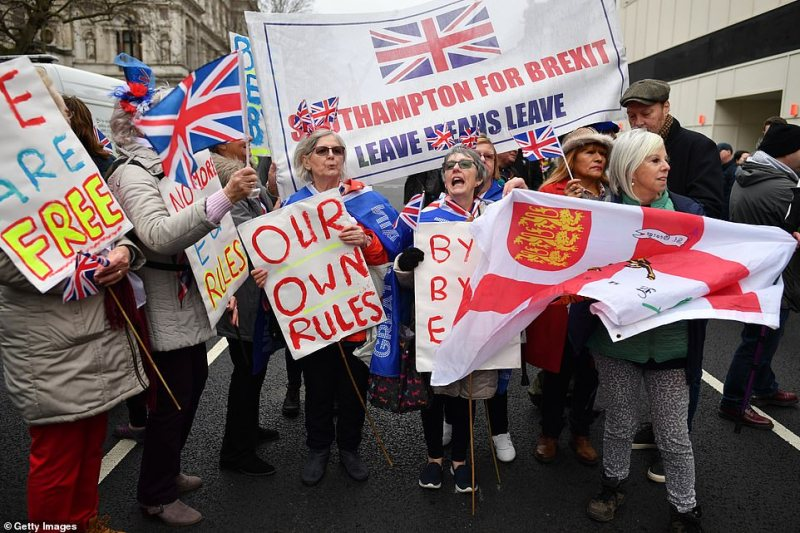 In London, pro-Brexit supporters wave Union Jack flags while standing on a European Union flag at Parliament Square. Many hold placards saying 'our own rules' and 'we are free' during the celebrations