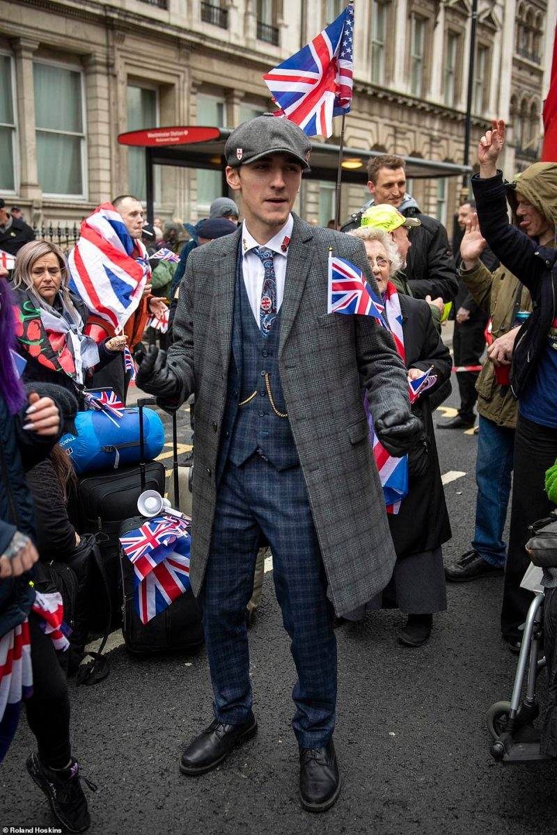 A suited man does his best to look the part among Brexiteers in central London today as Britons prepare to mark the country's departure from the European Union
