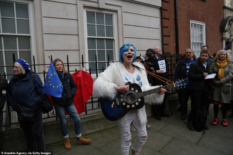 The woman, sporting blue stars on her face, sings and plays the guitar as part of a demonstration by remainers outside parliament