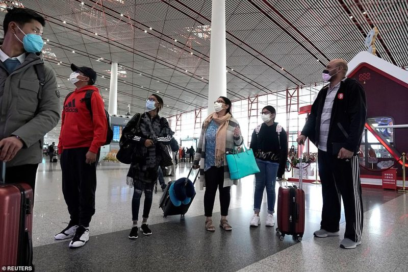 Foreign travellers wearing masks check their flight's departure information at Beijing International Airport in Beijing, China as the country is hit by an outbreak of the new coronavirus