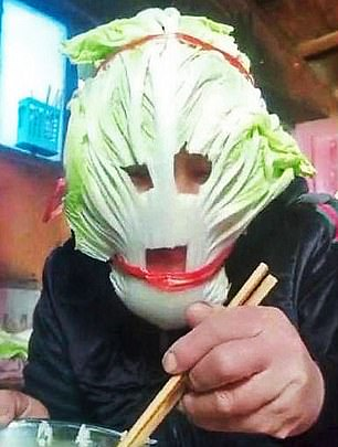 A man using lettuce leaves as makeshift protection
