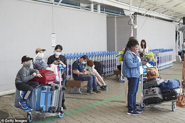 Passengers arriving at Auckland International Airport wear face masks amid the coronavirus epidemic