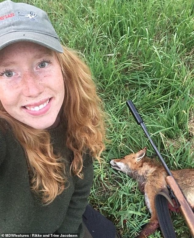 Trine smiles at the camera while standing over the corpse of a fox. The pair even hunt fox cubs, they said, in order to control their numbers