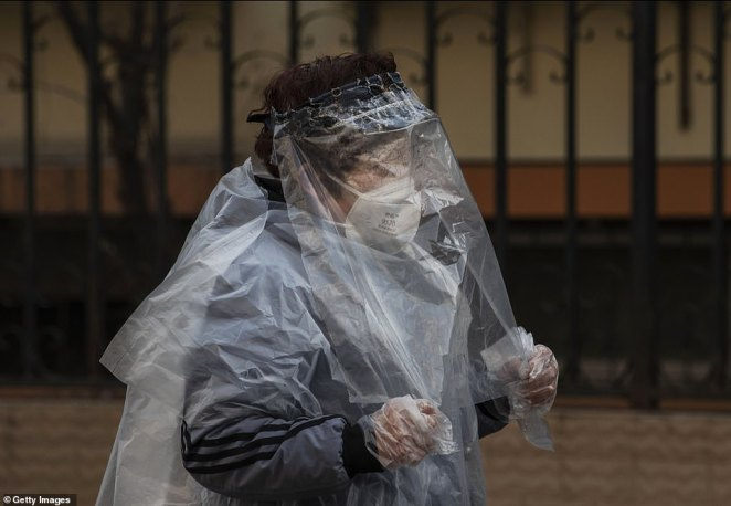 A Chinese woman wears plastic wrap and bags and a protective mask as she walks in a residential neighborhood in Beijing on Tuesday. The total number of cases in mainland China is officially 44,653, though many case may have gone uncounted