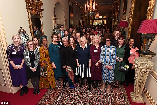 The Duchess of Cornwall poses with guests during a the reception at Clarence House in London yesterday