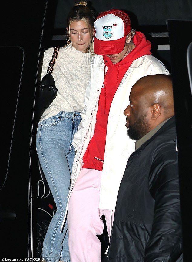 Cozy clothes: The two arrived in a chauffeured van, with Hailey covering up in a cream-colored cable knit sweater tucked into her high-waisted acid wash jeans