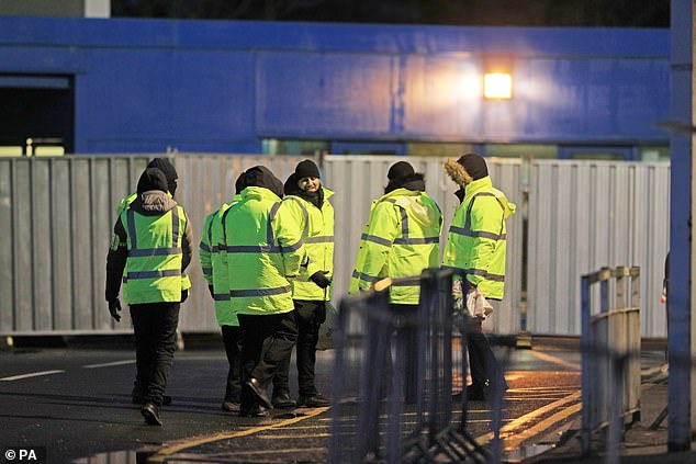 Staff in high-visibility jackets at the facility at Arrowe Park Hospital on Merseyside. 83 people who had been evacuated from China and put into quarantine there were sent home today