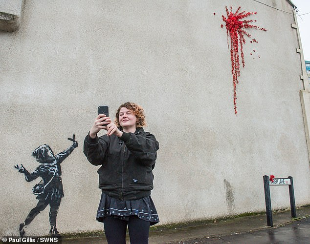 A resident is pictured taking a selfie with the artwork in the background