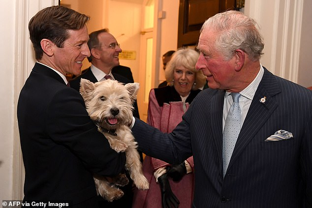Pictured: The Prince of Wales meets West Highland terrier Monty during the visit, as he is held by Darragh McElroy, head of national security communications
