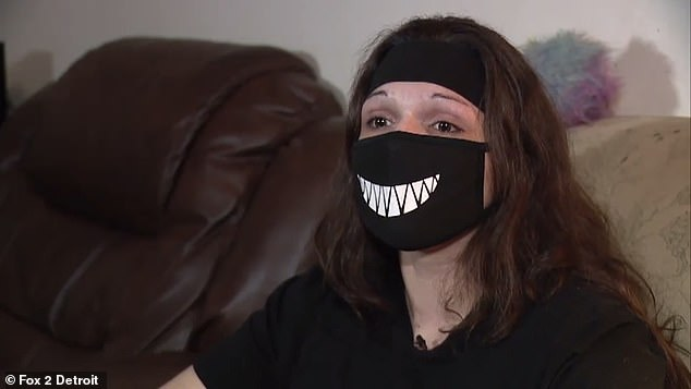 Amanda Ulmen claims she wears the black mask decorated with a smile of sharp white teeth to protect against the coronavirus because she has a weakened immune system