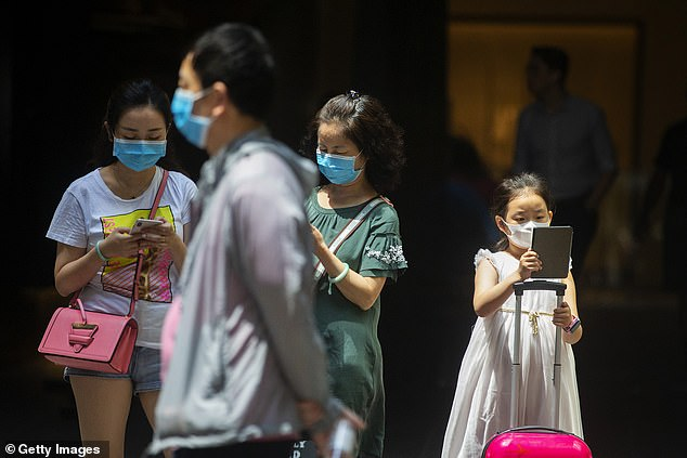 Almost a third of Australia's international students could be lost to other countries if the coronavirus travel ban remains in place from China. Pictured: people in Sydney wearing face masks in January following news about the coronavirus outbreak