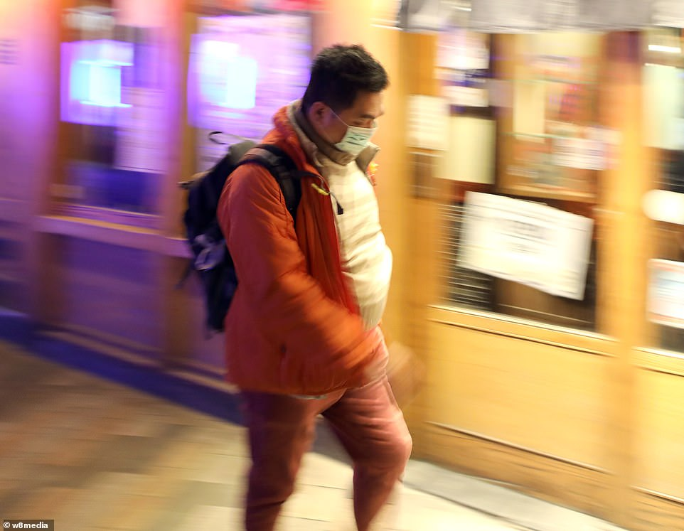 By January 8, 59 suspected cases had been reported and seven people were in critical condition. Tests were developed for the new virus and recorded cases started to surge. Pictured: A man wearing a protective face mask in China Town