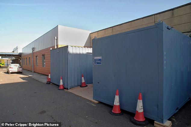 At Eastbourne District General Hospital, windowless shipping containers at the side of what appears to be a road in the hospital grounds are used