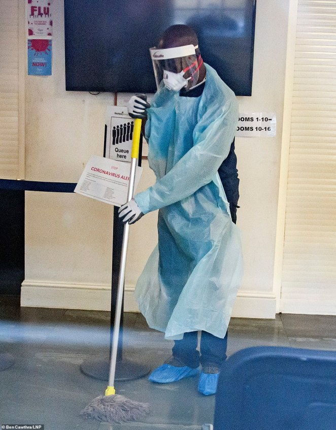 Pictured:A man in a medical mask cleaning surfaces inside Ritchie Street Health Centre in Islington, north London, on Thursday