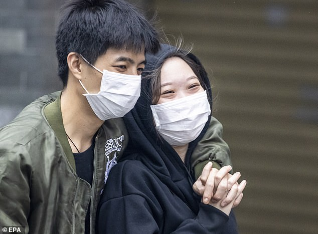 A couple wearing protective masks walks on the street on Valentine's Day in Guangzhou, China