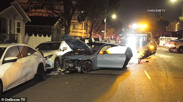 The front bumper of the BMW 4 Series is totally mangled as a tow truck prepares to load it in the early hours of the Thursday