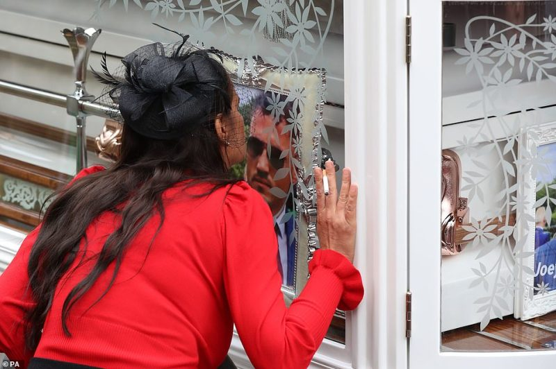 A woman is pictured kissing the picture of Joe Smith as she holds a cigarette in her hand dressed in bright red and black