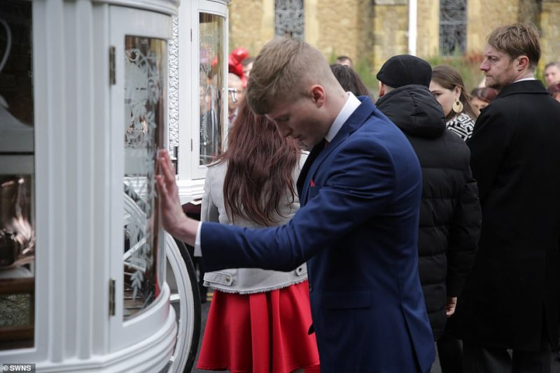 One young man struggled to contain his emotions as he placed his hands on one of the brothers' coffins outside the church