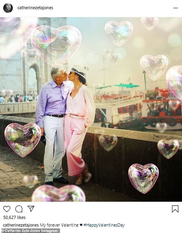 Still in love after all these decades: Catherine Zeta-Jones called her husband Michael Douglas her 'forever Valentine'; they were seen kissing with balloon bubbles floated around them